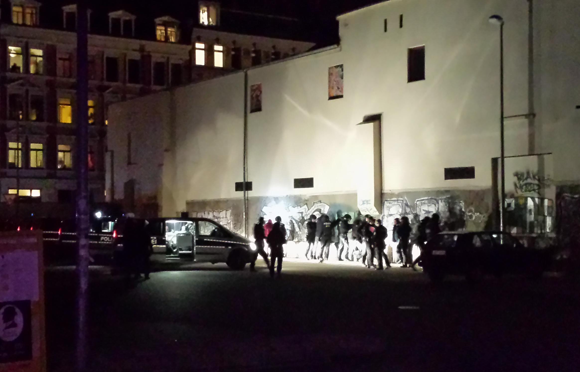 Polizei beginnt, Einzelne aus der Kundgebung herauszulösen und auf einem  Parkplatz zu durchsuchen. Personen