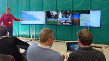 Männer verfolgen Testflüge/ Simulationen von Flugzeug-Drohnen im EU-Projekt RAID auf dem Monitor.