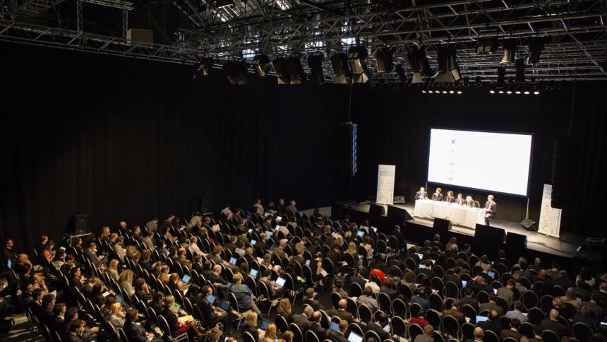 Großer Konferenzsall mit vielen vollen Stühlen.