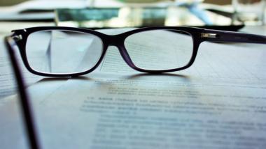 Brille auf einem Stapel Papier.