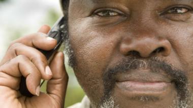 Ein Mann hält sich ein Handy ans Ohr.