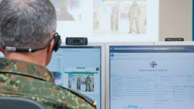 Ein Mann in Bundeswehr-Uniform sitzt vor PC-Bildschirmen