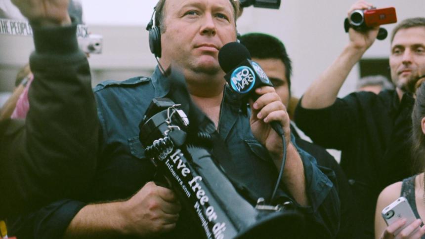 Alex Jones mit einem Megaphon in der rechten und einem Mikrophon in der linken Hand