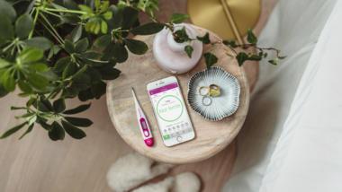 Ein Thermometer und ein Smartphone liegen auf dem Nachttisch