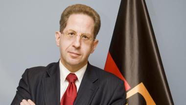 Hans-Georg Maaßen mit gekreuten Armen vor der Deutschlandflagge