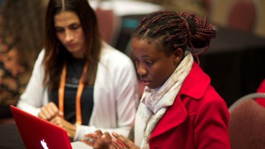 Ein junges Mädchen arbeitet auf einem Hackathon an ihrem Laptop