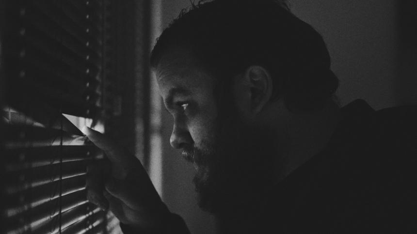 Ein Mann mit Bart späht mit dem Finger zwischen seiner Jalousie aus einem Fenster