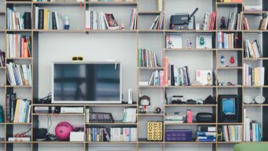 Wohnzimmer-Regal mit Flachbildschirm, Büchern und Gadgets.