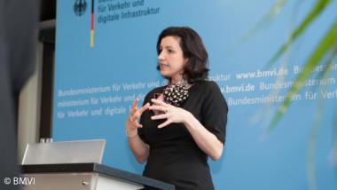 Dorothee Bär vor einer blauen Wand an einem Rednerpult beim Sprechen