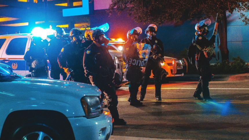 Auf einer dunklen straße stehen mehrere Polizisten vor Streifenwagen.