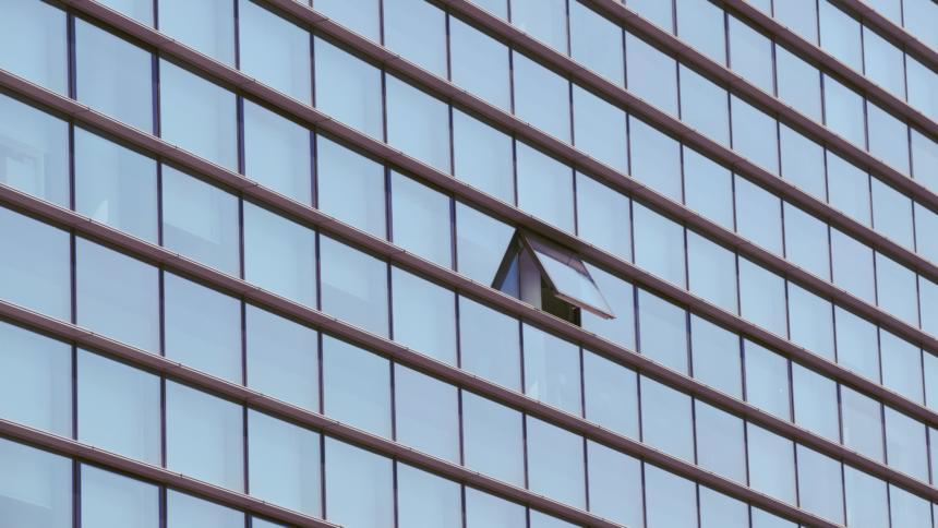 Eine Gebäudewand mit vielen Fenstern, eins ist offen.