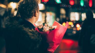 Ein Mann steht mit dem Rücken zum Betrachter mit einem Blumenstrauß an einer Straße