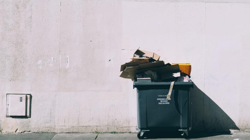Ein schwarzer Müllcontainer vor einer grauen Wand.