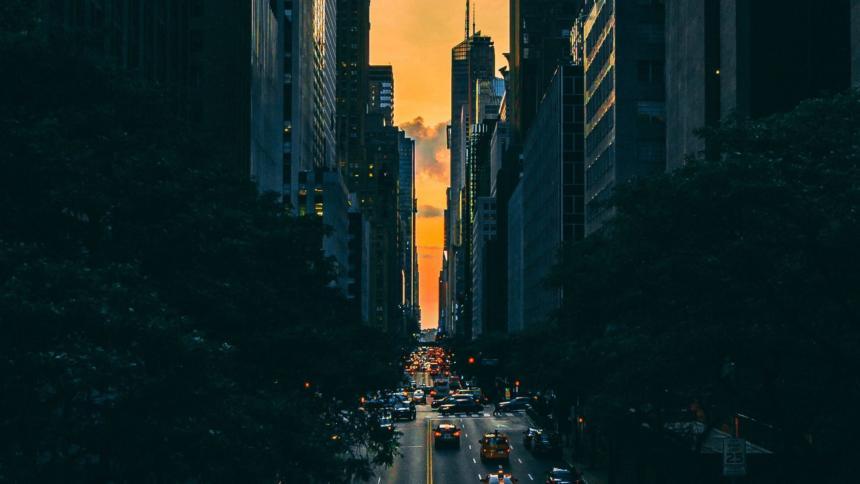 Bild einer großen Straße im Dunkeln, am Ende leuchtet der Himmel