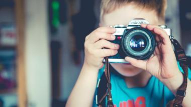 Ein Kind mit einer analogen Kamera vor dem Gesicht.
