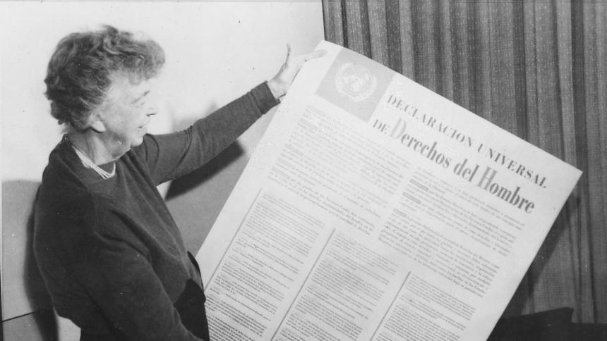 Ein schwarz-weißes Foto zeigt Eleanor Roosevelt, wie sie ein großes Blatt mit der Erklärung der Menschenrechte hält