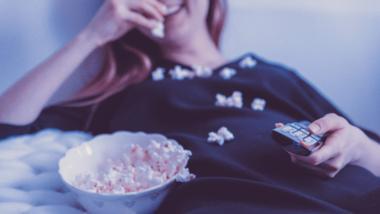 Frau beim Popcornessen auf dem Bett