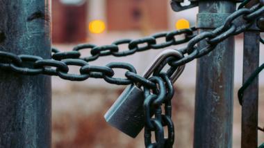 Ein Tor, das mit einer Metallkette und einem Vorhängeschloss verschlossen ist