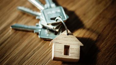 Ein Schlüsselbung mit einem Anhänger aus Holz, der ein Haus darstellt, auf einem hölzernen Untergrund