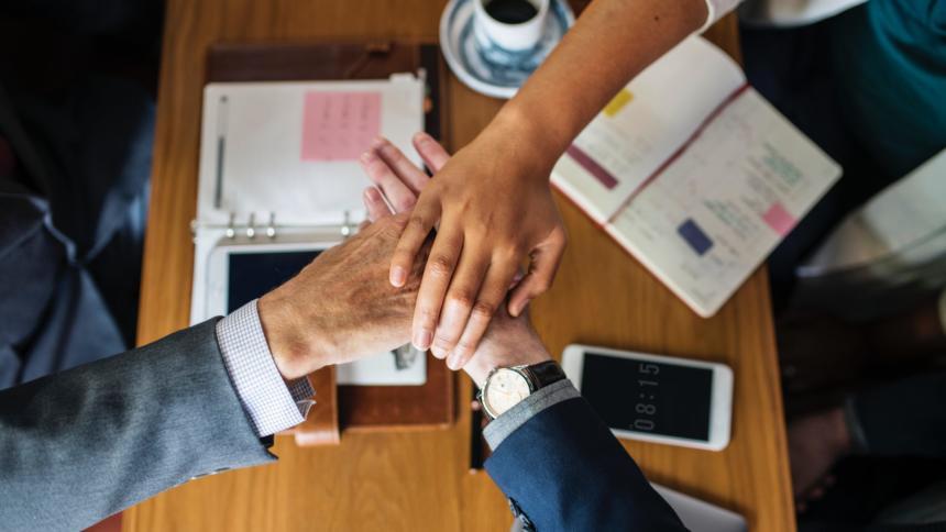 Über einem Tisch mit verschiedenen Schriebwaren und einem Handy, schlagen drei Hände zusammen ein.