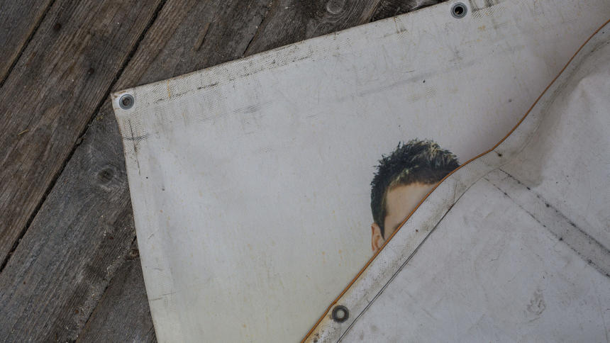 Mann versteckt sich hinter Plakat