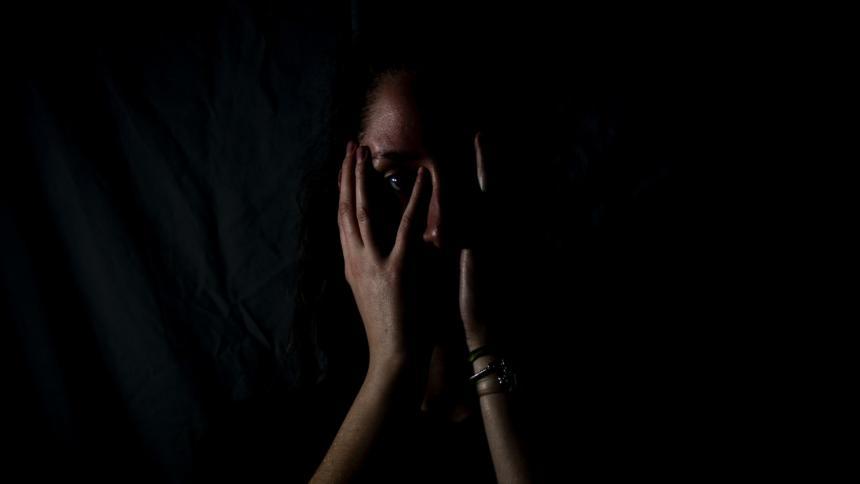 Eine Frau hält sich die Hände vor das Gesicht, schwarzer Hintergrund