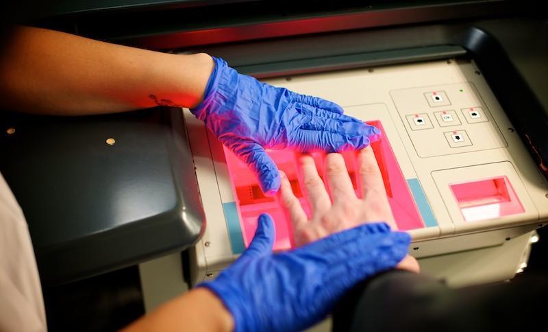 Die britische Polizei beim Fingerabdrücke-Nehmen