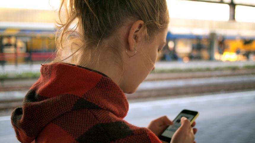 Frau mit Handy am Bahnsteig