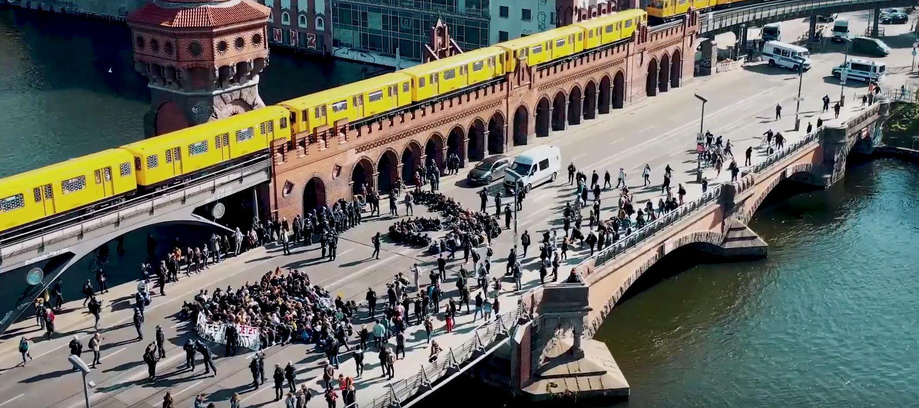 Menschen sitzen aus Protest auf der Oberbaumbrücke in Berlin.