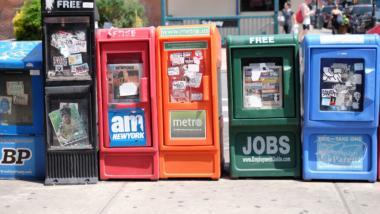 Aufgereihte Straßenzeitungsverkaufscontainer in unterschiedlichen Farben.