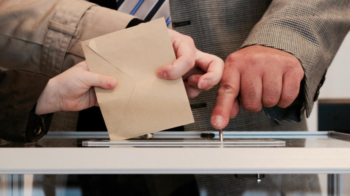 Jemand wirft einen braunen Briefumschkag i eine Wahlurne.