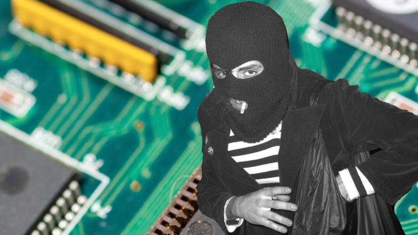 Mann mit Sturmhaube, im Hintergrund eine Platine mit Computerchips