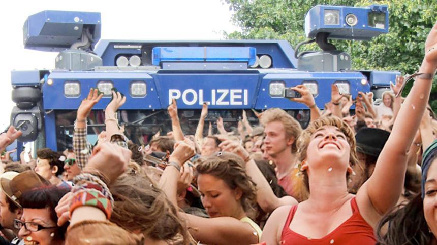Tanzende Leute, im Hintergrund ein blauer Wasserwerfer der deutschen Polizei