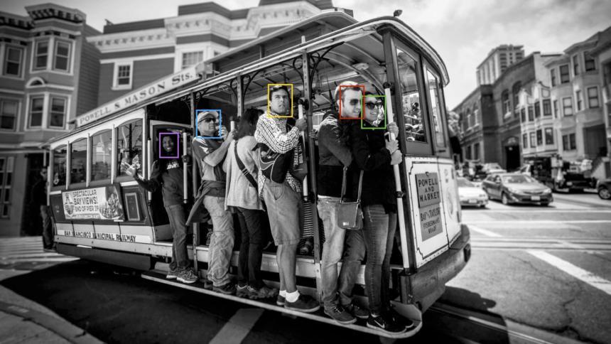 Menschen fahren mit der Straßenbahn in San Francisco. Ihre Gesichter sind mit bunten Kästen markiert, die Gesichtserkennung symbolisieren soll.