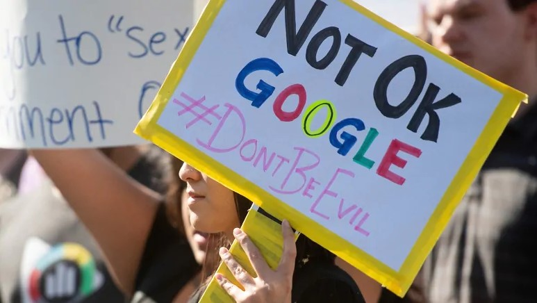 Frau hält Schild hoch, auf dem steht Not Okay Google