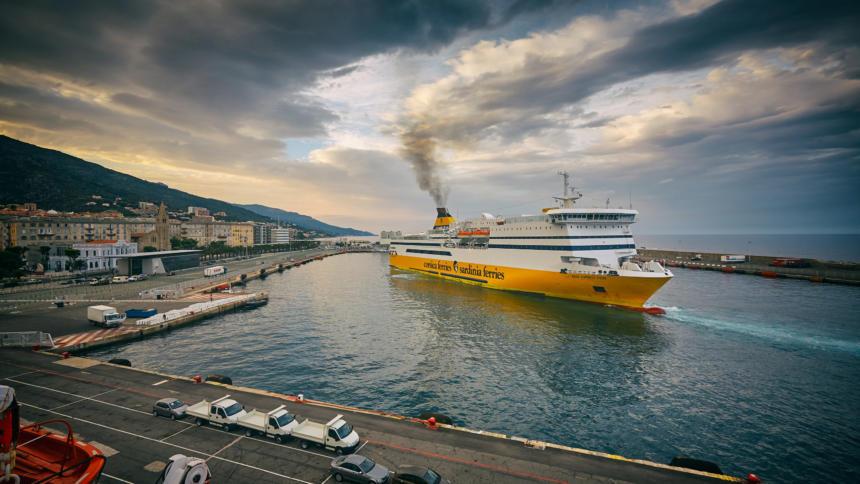 Eine gelbe Fähre im Hafen von Bastia. Aus dem Schornstein steigt Rauch auf.