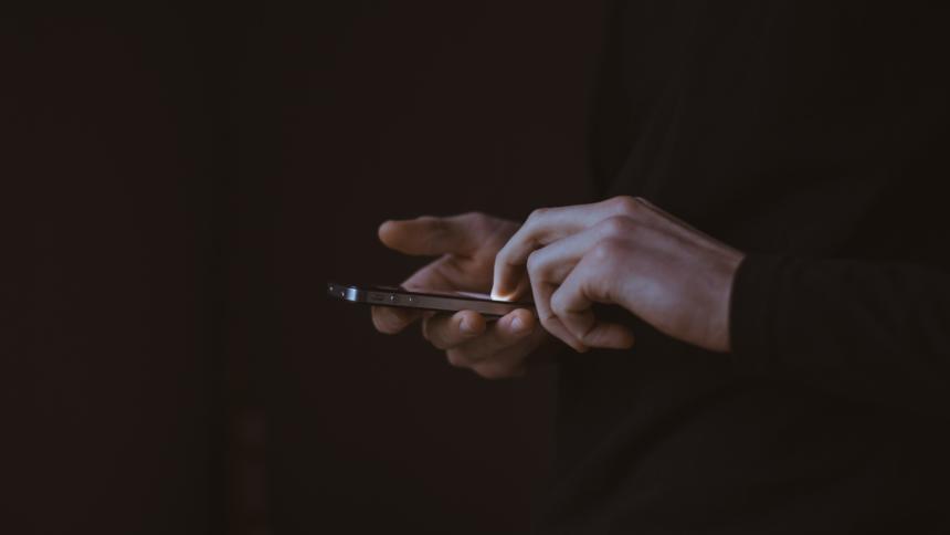 Hände halten ein Smartphone vor dunklem Hintergrund
