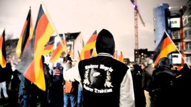 Deutschlandfahnen, im Vordergrund ein Rechtsradikaler mit Nazi-Pullover