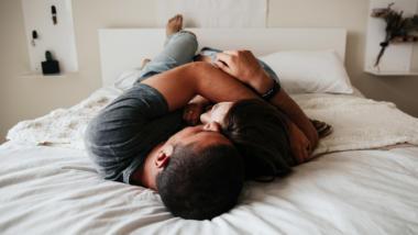 Paar liegt im Bett.