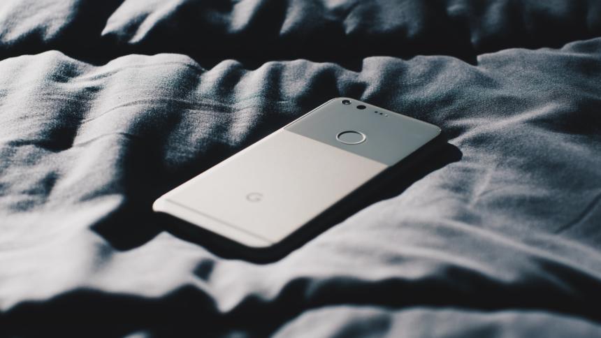 Handy liegt auf Bettdecke