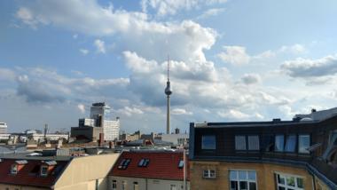 Der Berliner Fernsehturm, drapiert vor einem Hintergrund aus fluffig-losen Wolken