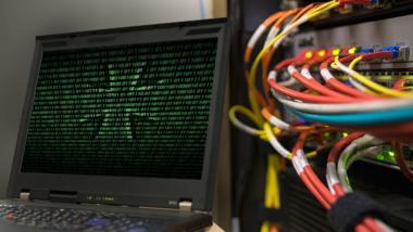 Bildmontage zeigt Kabelanschlüsse an einem Rechner und das Eiserne Kreuz hinter einem Binärcode auf einem Laptop