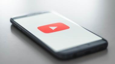 Smartphone, Bildschirm zeigt YouTube-Logo auf weißem Hintergrnud