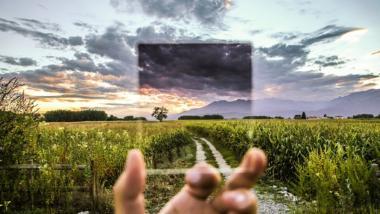 Eine Hand hält einen Glasfilter vor einer Landschaft