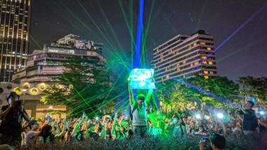 Menschen protestieren in Hongkong mit Laserpointern, im Hintergrund Hochhäuser