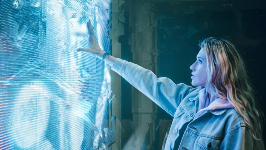 Eine junge Frau steht vor einer blau leuchtenden Kunstinstallation und streckt ihren Arm danach aus.