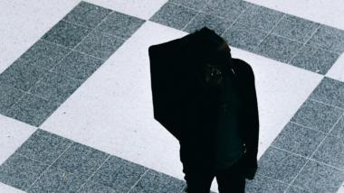 Die schwarze Silhouette eines abgestiegenen Deliveroo-Fahrers auf schwarz-weißem Kachelboden