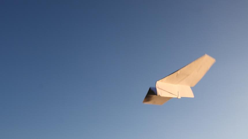 Ein Papierflugzeug vor blauem Himmel