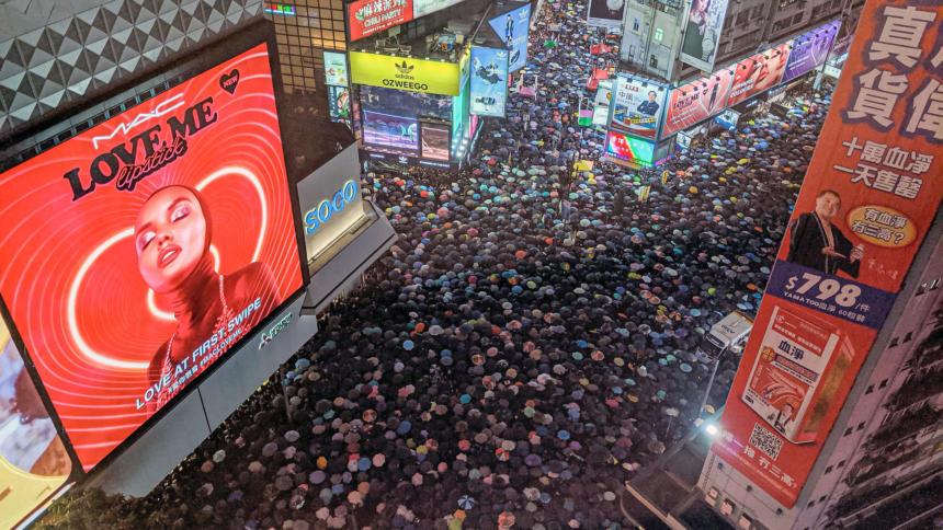 Proteste in Hongkong, im Hitergrund Werbetafeln und Hochhäuser