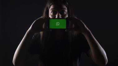 Ein Frau hält sich ein Smartphone mit dem WhatsApp-Logo vor den Mund.